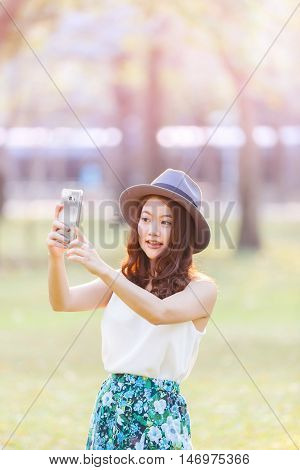 Beautiful asian woman smiling with perfect smile in a park and selfie by smartphone in her hand. selective soft focus