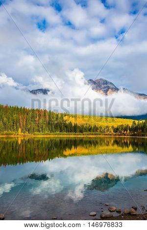 Patricia Lake amongst the forests, yellow bushes and mountains. Autumn in the Rocky Mountains of Canada