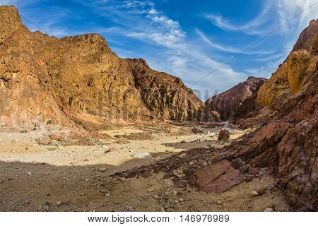 Israeli warm winter. Picturesque and multi-color Black canyon in ancient Eilat mountains