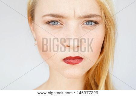 Angry sad red-haired woman portrait. Young female with very serious and blaming look, pursed lips. Angry, frowning, grumpy carroty girl close-up.