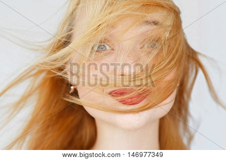 Excited foxy woman portrait, smiling at camera. Jumping girl face, covered with red hair. Fun, happyness, fooling concept