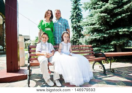 Happy Family At First Holy Communion Sitting On Bench Background Church. Mother With Sun And Daughte