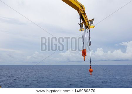 Crane boom and crane lighting in the sea with sky and clouds background on offshore platform.