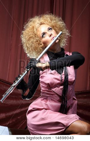 Beautiful and sexy Flautist surrounded by music scores