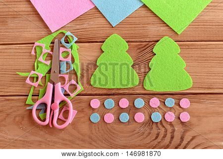 How to sew Christmas decoration. Step. Felt Christmas tree patterns, felt scraps, scissors on wooden background. Homemade crafts. Winter needlework project for children. Top view