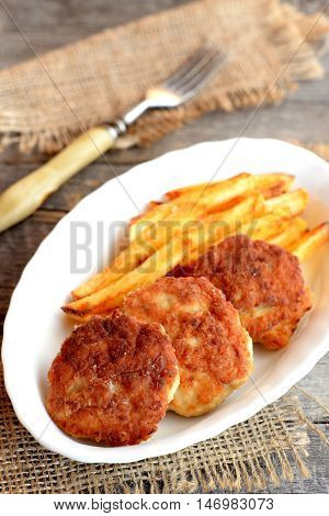 Minced meat cutlets and fries on a plate, fork and burlap on old wood background. Cutlets made with Turkey fillets and fried in vegetable oil. Recipe photo. Closeup