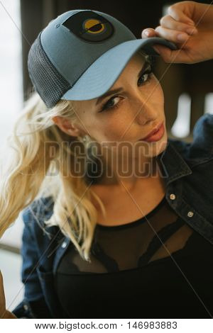 cute long-haired girl in jeans jacket and baseball cap holds for blond hair. Pulls hands behind his tail and looking at the camera.