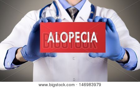 Doctor's hands in blue gloves shows the word alopecia. Medical concept.