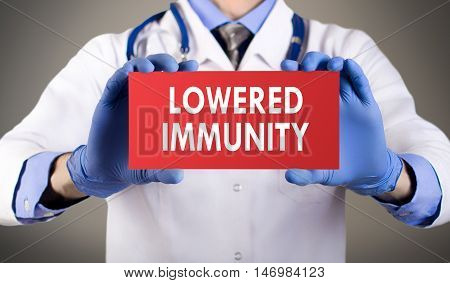 Doctor's hands in blue gloves shows the word lowered immunity. Medical concept.
