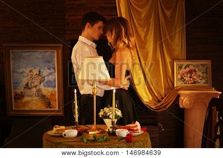 Couple in love dancing and kissing into luxary restaraunt. Romantic evening interior for loving couple.