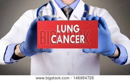 Doctor's hands in blue gloves shows the word lung cancer. Medical concept.