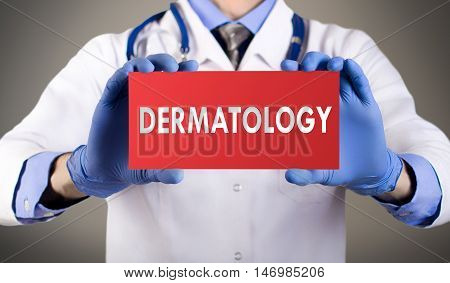 Doctor's hands in blue gloves shows the word dermatology. Medical concept.