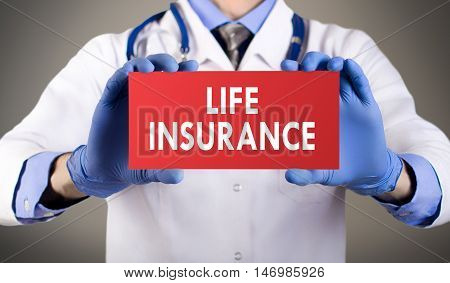 Doctor's hands in blue gloves shows the word life insurance. Medical concept.
