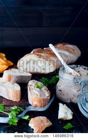 mousse, pate in a jar with a baguette and parsley on a wooden background dark