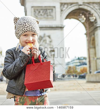 Happy Child Near Arc De Triomphe In Paris Eating French Macaroon