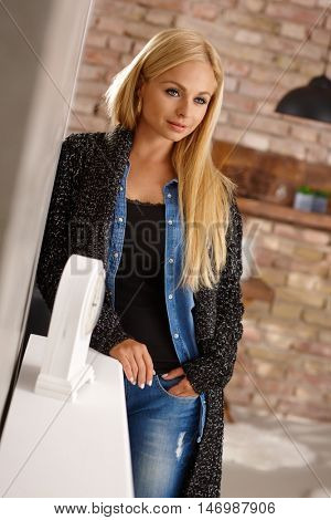 Thoughtful young blonde woman standing against wall.