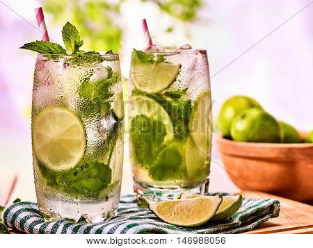 Alcohol drink. On wooden boards two glasses with alcohol drink and ice cubes. Drink number forty seven cocktail mohito and mint leaf. Country life. Light background.