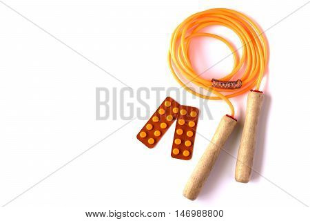Orange jump rope with blisters of pills on white background. Healthy living concept.