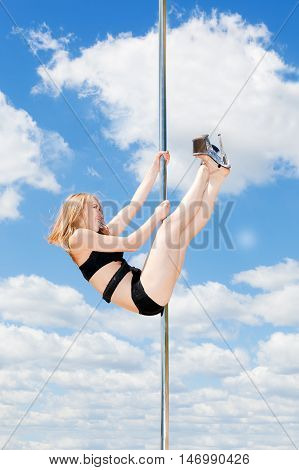 Blond Dancer Performing Acrobatic On Pole Against Blue Sky