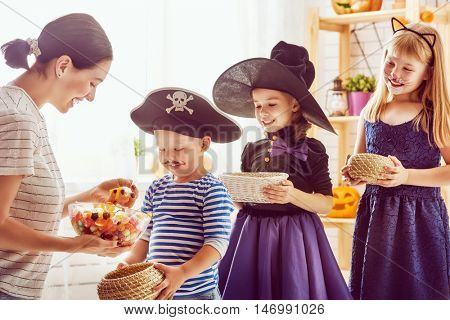 Happy family celebrating Halloween! Young mom treats children with candy. Funny kids in carnival costumes.