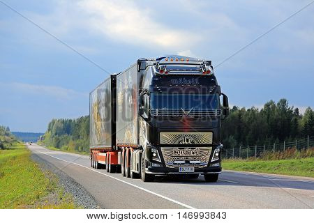 ORIVESI FINLAND - SEPTEMBER 1 2016: The specatular show truck Volvo FH16 750 Ace of Spades moving along road in Central Finland under dark overcast sky.
