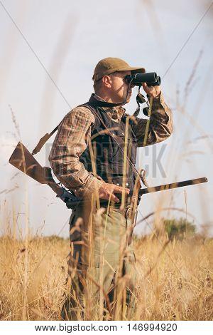 Man hunter with shotgun looking through binoculars in forest