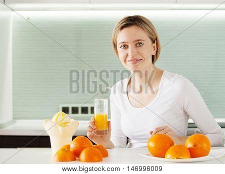 Adult woman cooking orange juice on juicer