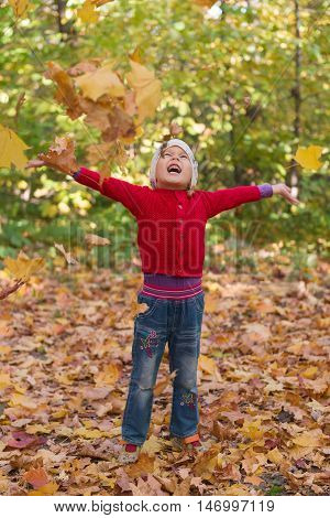cheerful child among the falling leaves around