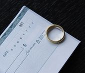 stock photo of dowry  - a ring and an open checkbook on a black desk - JPG