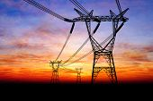 image of transformer  - Electricity pylons and power lines at orange sunset - JPG