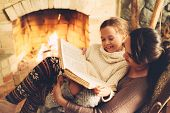 Mom with child reading book and relaxing by the fire place some cold evening, winter weekends, cozy  poster