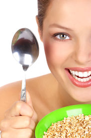 picture of healthy eating girl  - Pretty smiling woman holding a spon and a plate with cereal - JPG