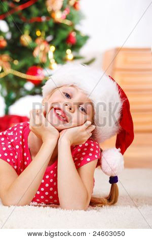 Portrait of a laughing girl in Santa hat lying on carpet