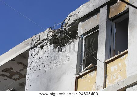 Hole and broken windows in the apartment building caused by explosion of missile launched by Hamas terrorists.
