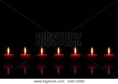 Burning Red Candles In Front Of Black Background