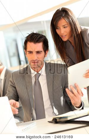 Business team using electronic tablet at work