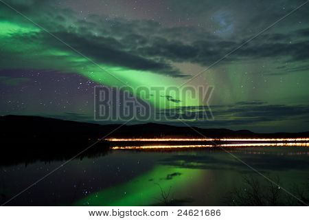 Stars and Northern Lights over dark Road at Lake