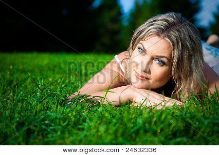 attraktive Frau auf grünem Gras liegend