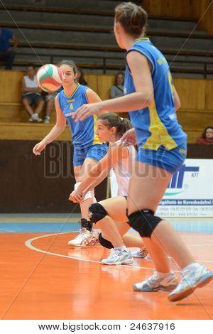 KAPOSVAR, HUNGARY - OCTOBER 2: Julia Schrauff (in white) in action at a Hungarian NB I. volleyball game Kaposvar (yellow number) vs Tatabanya (white number), October 2, 2011 in Kaposvar, Hungary.
