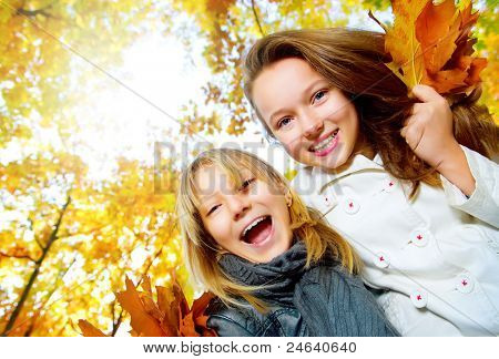 Beautiful Teenage Girls Having Fun in Autumn Park .Outdoor