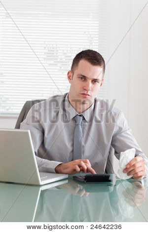 Young businessman checking an invoice