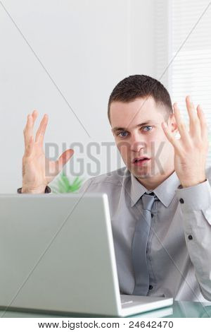 Close up of unhappy young businessman having problems with his notebook