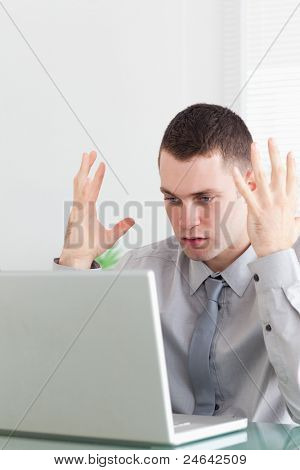 Close up of unhappy young businessman having problems with his laptop