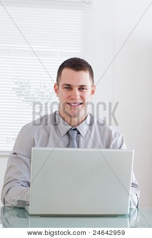 Close up of smiling young businessman working on his laptop