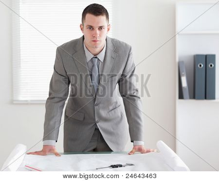 Architect standing behind a table with plans in front of him