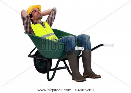 Construction worker resting in a wheelbarrow