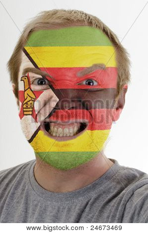Face Of Crazy Angry Man Painted In Colors Of Zimbabwe Flag