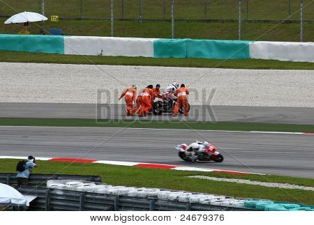 SEPANG, MALAYSIA - OCTOBER 23: Track staffs assist Moto2 rider Randy Krummenacher after he crashed out during warm up of the Malaysian Motorcycle GP 2011 on October 23, 2011 at Sepang, Malaysia.