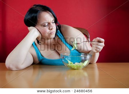 Unhappy Overweight Woman With Her Meal, A Bowl With A Few Leaves Of Lattuce In It. Diet Concept.