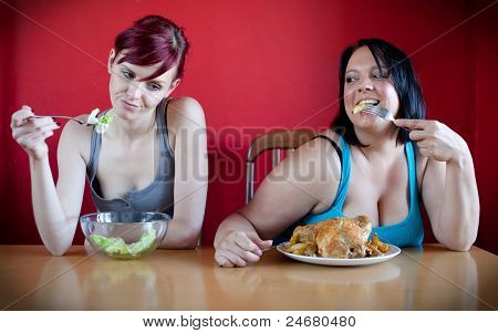 On A Diet. Skinny Woman Eating A Few Leaves Of Lettuce While The Overweight Woman Is Eating Whole Ch